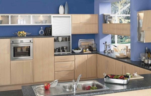 Tường bếp màu xanh nước biển làm với kệ màu nâu gỗ nhạt.