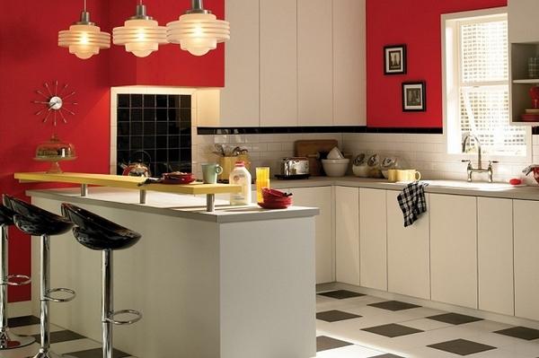Nhà bếp kết hợp khu vực ăn với tường sơn màu đỏ ấn tượng và tủ bếp trắng tinh khôi.